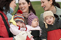 Three mothers with babies in slings chatting outdoors
