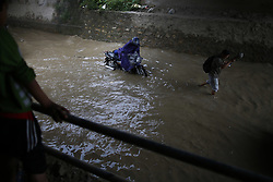 August 27, 2017 - Lalitpur, Nepal - A pillion walks along after a motorbike clogged functioning on an inundated road after a spell of heavy rainfall in Lalitpur, Nepal on Sunday, August 27, 2017. (Credit Image: © Skanda Gautam via ZUMA Wire)