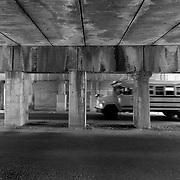 School bus passing under train bridge at Summit Street near Southwest Boulevard, Kansas City, Missouri.