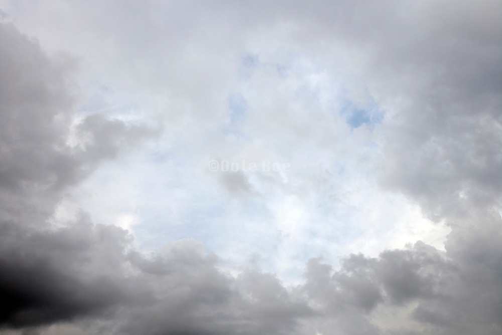 gray clouds making way for a blue sky