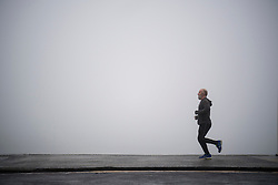 © London News Pictures. 08/01/2016. Aberystwyth, UK. A man jogs through thick fog and and sea mist on the coastline at Aberystwyth seafront at the start of the day on Sunday 8 Jan 2016. The mild damp weather is set to change later in the week with a plume of cold northerly  air bringing snow to many areas. Keith Morris/LNP