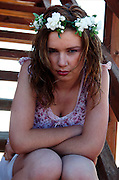 A disappointed young blond teen model with flowers in her hair sitting on wooden stairs