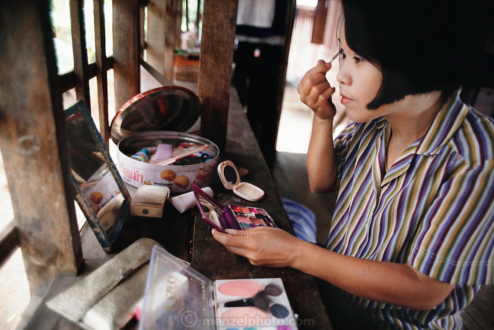 Early in the morning, Buaphet Khuenkaew applies makeup in the tiny two-room wooden house she and her family live in, in Ban Muang Wa village, outside the northern town of Chiang Mai, in Thailand. The house is on stilts to protect it from yearly flooding, and is surrounded by rice fields. Material World Project.