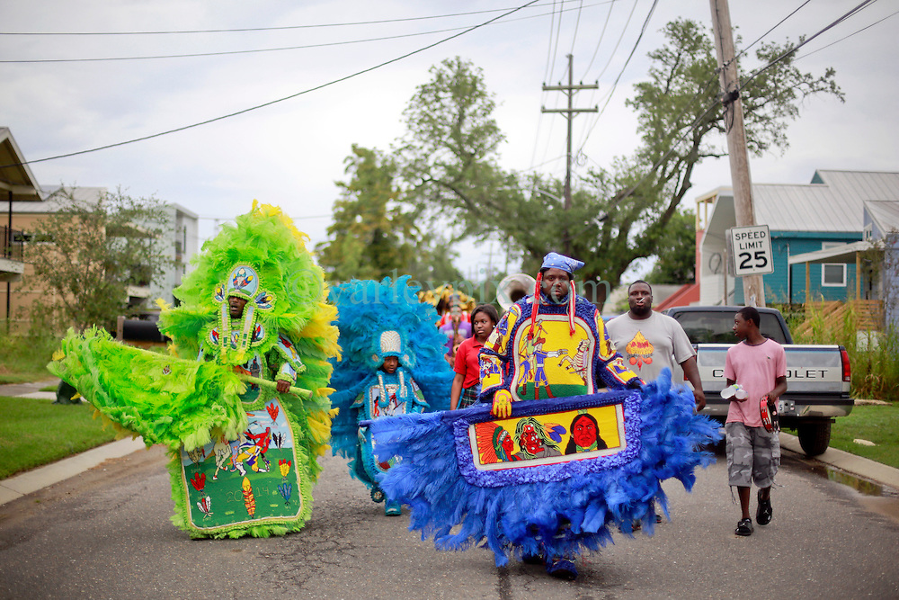 29 August 2014. Lower 9th Ward, New Orleans, Louisiana. <br /> Survivors of the storm. Mardi Gras Indians (L/R) Robert 'Flag Boy Slim' Stevenson of the Hard Head Hunters, Michael 'Spy Boy' Tenner (10 yrs) of the Comanche Hunters and Herbert Motton of the Hot Head Hunters lead a touching second line parade along Tennessee Street in the Lower 9th Ward in memory of those who perished in the storm 9 years ago. <br /> Photo; Charlie Varley/varleypix.com