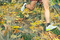 Young woman seen from waist down jogging in fall colors.