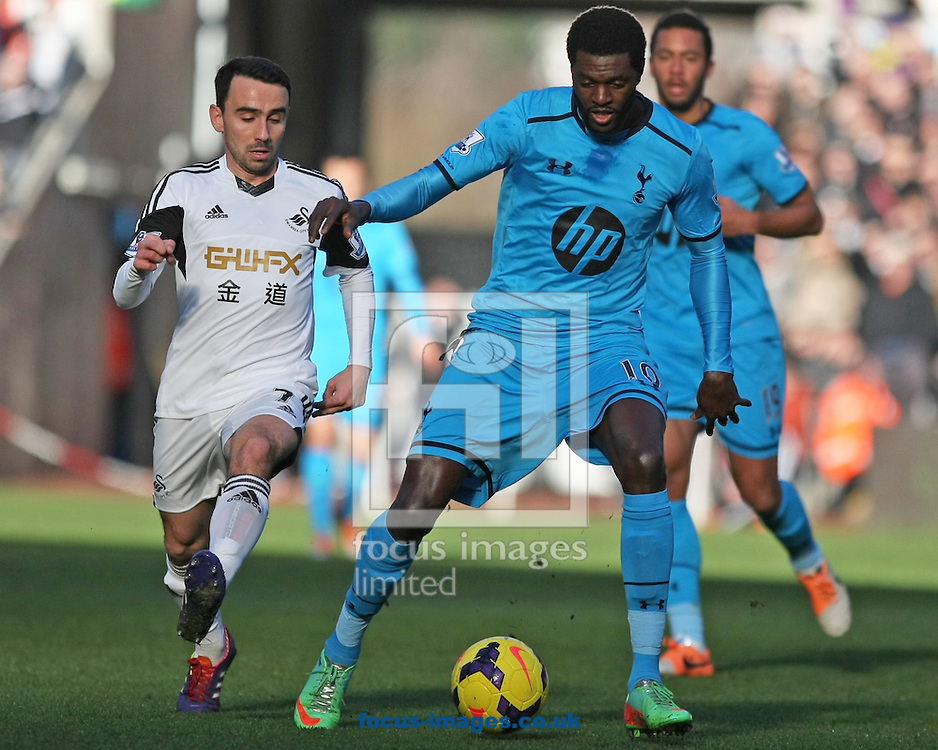 Picture by Mark Hawkins/Focus Images Ltd 07949 023795<br /> 19/01/2014<br /> Leon Britton of Swansea City and Emmanuel Adebayor of Tottenham Hotspur during the Barclays Premier League match at the Liberty Stadium, Swansea.