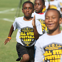Christian Brown, 7, runs sprints as a warm up Saturday at the All-Star Football Camp for the Boys and Girs Club