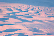 sunset light on abstract patterns in snow