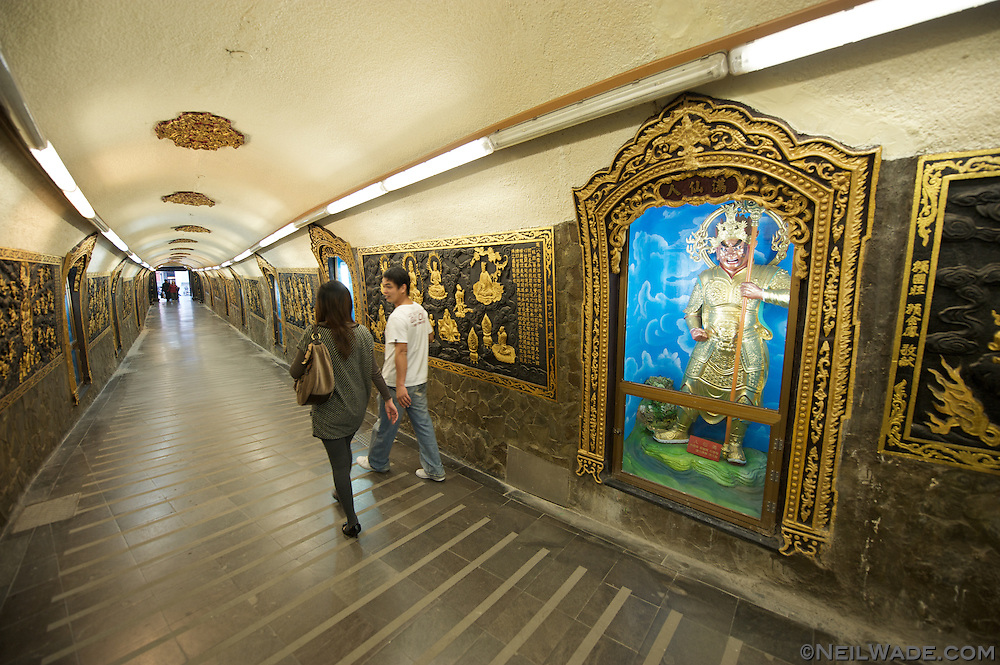 A couple walks through a hallway into Guandu Daoist Temple in Taipei, Taiwan.