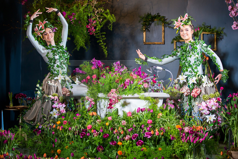 © Licensed to London News Pictures. 25/04/2018. Harrogate UK. Dancer Alison Parsons (left) & Georgia Paton Durrant (right) wear flower dresses in bathroom of the Green House display at this years Harrogate Flower Show in which starts tomorrow.  The GREENhouse has been designed to blur the lines between house and garden, creating a home infused with nature complete with living wallpaper,cascading flower shower, an aromatic bed of herbs and even a vege-table. Photo credit: Andrew McCaren/LNP