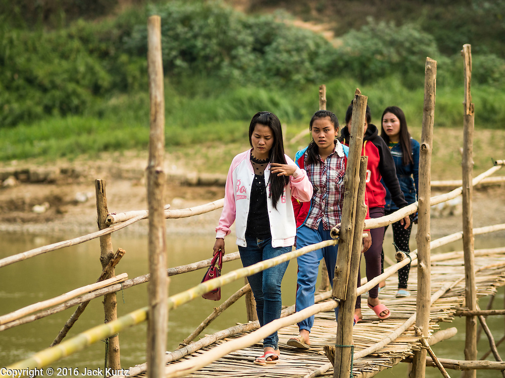 12 MARCH 2016 - LUANG PRABANG, LAOS:  Tourists cross a bamboo foot bridge across the Nam Khan River near Luang Prabang. The bridge is seasonal. Villagers put it up every year, at the at the start of the dry season and take it down when the Nam Khan floods during the rainy season.  Laos is one of the poorest countries in Southeast Asia. Tourism and hydroelectric dams along the rivers that run through the country are driving the legal economy.     PHOTO BY JACK KURTZ