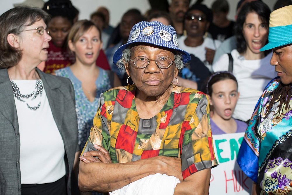 Carnell Holley of Charlotte awaits the transfer of demonstrators in custody behind the North Carolina Legislative Building along with hundreds of others who sang songs and cheered on their act of civil disobedience on Monday, May 20, 2013.