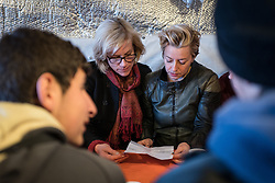 © London News Pictures. Calais, France. 04/03/16. Actress Juliet Stevenson (left), Producer Tracey Seaward (right) look at the asylum papers of an unaccompanied Syrian boy who lives in the Calais 'Jungle' camp and has family in Britain. They are the first celebrities to join the Citizens UK and Help Refugees 'buddy scheme' which aims to put pressure on the British government to allow unaccompanied minors in the Calais 'Jungle' to be reunited with their families in the United Kingdom.   Photo credit: Rob Pinney/LNP