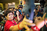03 MARCH 2013 - BANGKOK, THAILAND: .A Pheu Thai supporter attacks a television set with her shoes when it was announced on TV that MR Sukhumbhand Paribatra, the incumbent running on the Democrat ticket, had won the election for Bangkok governor. Pongsapat Pongchareon, running on the Pheu Thai ticket, lost the Bangkok's Governor's race to MR Sukhumbhand Paribatra, the incumbent running on the Democrat ticket. Sukhumbhand won the race after scoring a record number of votes, more than 1.2 million to Pongsapat's 1 million. The results were seen as an upset even though Sukhumbhand was the incumbent because all of the pre-election polls and the exit polls conducted on election day showed Patsapong winning.     PHOTO BY JACK KURTZ