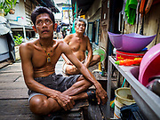 11 JULY 2017 - BANGKOK, THAILAND: Men sit on the sidewalk in front of their homes in a community built over the Chao Phraya River south of Krung Thon Bridge. The residents of the community expect to be evicted and their homes destroyed to make way for the city's plan to build a 14 kilometer long (22 mile) riverfront promenade. Thousands of families are expected to be evicted to accommodate the promenade. The riverside communities, built on stilts over the water, are prone to flooding and the city has been trying to control them for years. The houses are the only affordable housing for available to some of the poorest people in Bangkok.      PHOTO BY JACK KURTZ