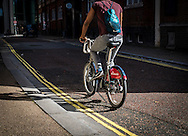 Cyclist riding a Santander Hire Bicycle through London, Britain 25 Sep 2016