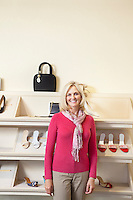 Portrait of a mature woman standing in front of footwear in shoe store