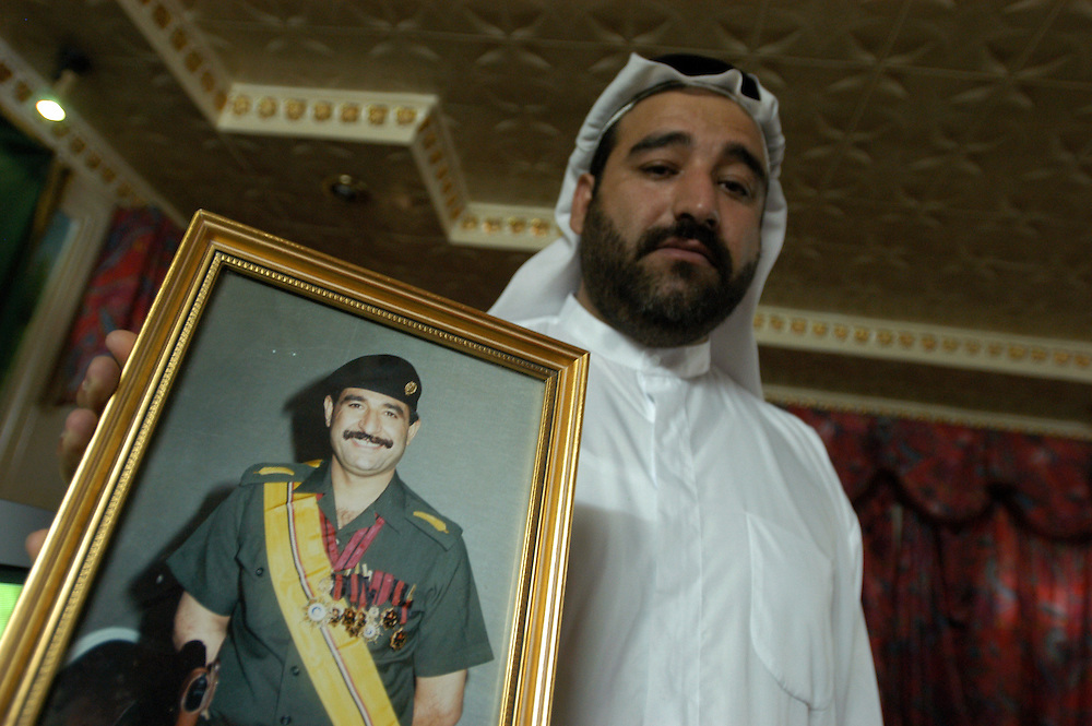 Jamal Kamel, holding a picture of his brother Hussein Kamel. Hussein and their other brother Saddam where married to Saddam Hussein's daughters Raghd and Rana. The two brothers were killed, along with 15 members of their family, by Saddam Hussein after they had fled to Jordon and returned to Iraq. The Kamel brothers are also nephews of Ali Hassan al-Majid, infamously known as Chemical Ali..Baghdad, Iraq. 30 May 2003..Photo © J.B. Russell