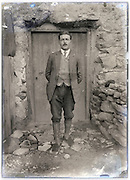 eroding glass plate with a young adult man standing in front of closed door