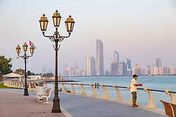 Man fishing from Corniche with view of skyline of Abu Dhabi United Arab Emirates