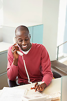 Mid-adult male office worker at desk talking on phone