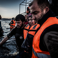 Lesvos Island 01-12-2015 Arrivals of migrants and refugees on the Greek island of Lesvos from the nearby Turkish coast; Volunteers face a difficult recovery from a boat loaded with refugees arriving at the early dawn lights on the Greek island of Lesvos