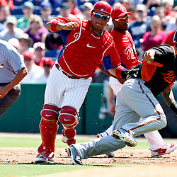 March 25, 2012; Clearwater, FL, USA; Philadelphia Phillies catcher Carlos Ruiz (51) tags out Baltimore Orioles second baseman Robert Andino (11) on a run down during the top of the first inning of a spring training game at Bright House Networks Field. Mandatory Credit: Derick E. Hingle-US PRESSWIRE