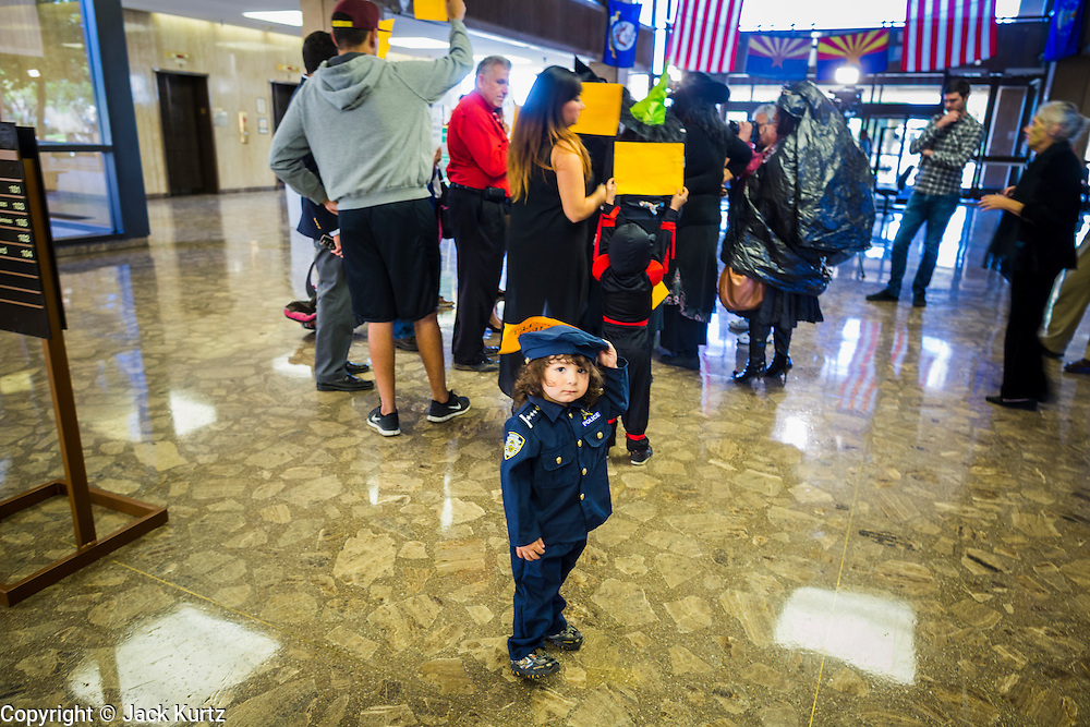 31 OCTOBER 2013 - PHOENIX, AZ:   A child wearing the Halloween costume of a police officer walks through the lobby of the Arizona state capitol during an immigration protest in the capitol Thursday. About 20 supporters of the DREAM Act and the deferred action program of President Barack Obama visited the office of Arizona Governor Jan Brewer to protest her decision to deny drivers licenses to Arizona DREAMERS and immigrants granted deferred action status by immigration authorities. The protest was a part of ongoing series of actions by immigration rights activists in Arizona to protest against anti-immigrant actions taken by Arizona political leaders.   PHOTO BY JACK KURTZ