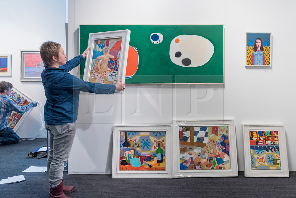 © Licensed to London News Pictures. 16/01/2018. LONDON, UK. Staff from the Edgar Modern gallery in Bath prepare their display stand.  Preview day of the 30th anniversary of the London Art Fair.  The fair launches the international art calendar with modern and contemporary art from leading galleries around the world and is taking place at the Business Design Centre, Islington from 17 to 21 January 2018.   Photo credit: Stephen Chung/LNP