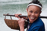 CHINA, Guangxi Province. But in fact this is very near the border with Guizhou Province. A Dong woman is smiling while carrying a small basket on a shoulder pole.  From Sanding village.