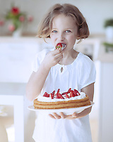 Young girl with cake and strawberries