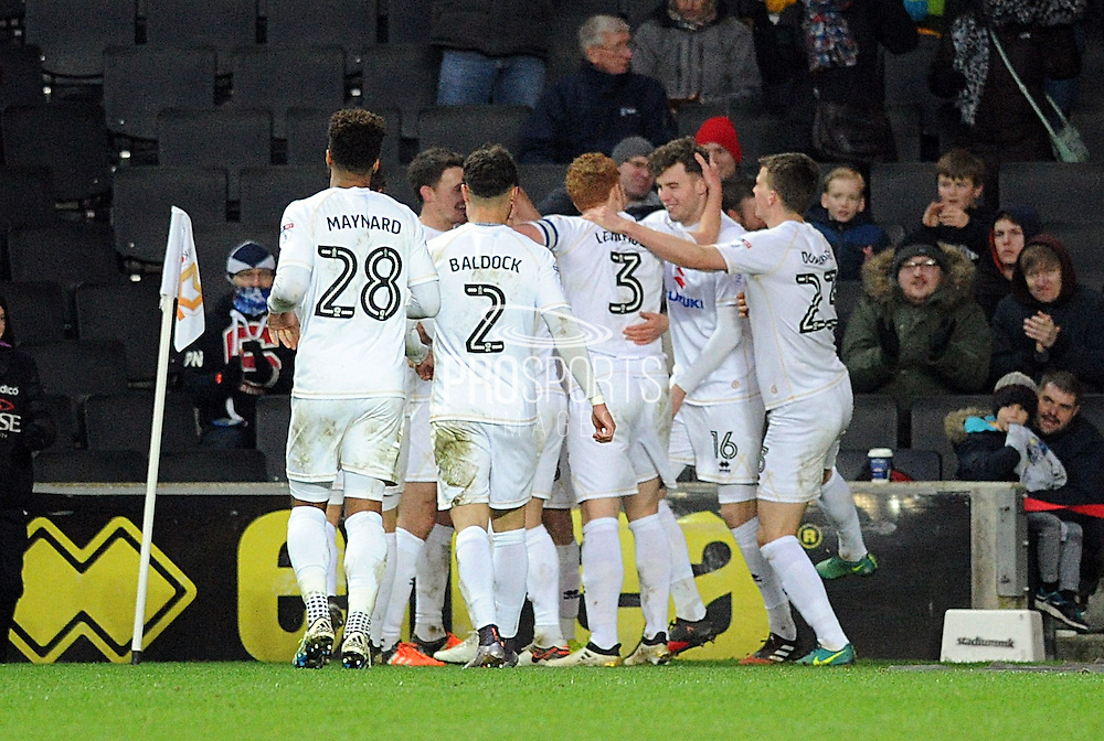 Dons players mob Robbie Muirhead of MK Dons (18) after he scored on debut during the EFL Sky Bet League 1 match between Milton Keynes Dons and Northampton Town at stadium:mk, Milton Keynes, England on 21 January 2017. Photo by Andy Handley.