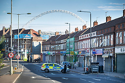 © Licensed to London News Pictures. 06/07/2019. London, UK. A police car is parked on the Harrow Road near Wembley Stadium after a man was shot on Friday night. The victim, believed to be a man in his 30s, was found with fatal gun shot wounds at 8pm near a mosque. No arrests have so far been made. Photo credit: Peter Macdiarmid/LNP