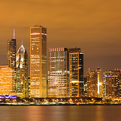 Chicago by night with the Aon Center, Prudential Towers, Trump Tower, Blue Cross Blue Shield, Smurfit Stone, and Hancock Center buildings along Lake Michigan shoreline