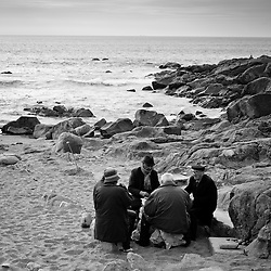 Men playing cards on a beach near Porto, Portugal