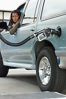 Woman sitting in car looking at fuel pump
