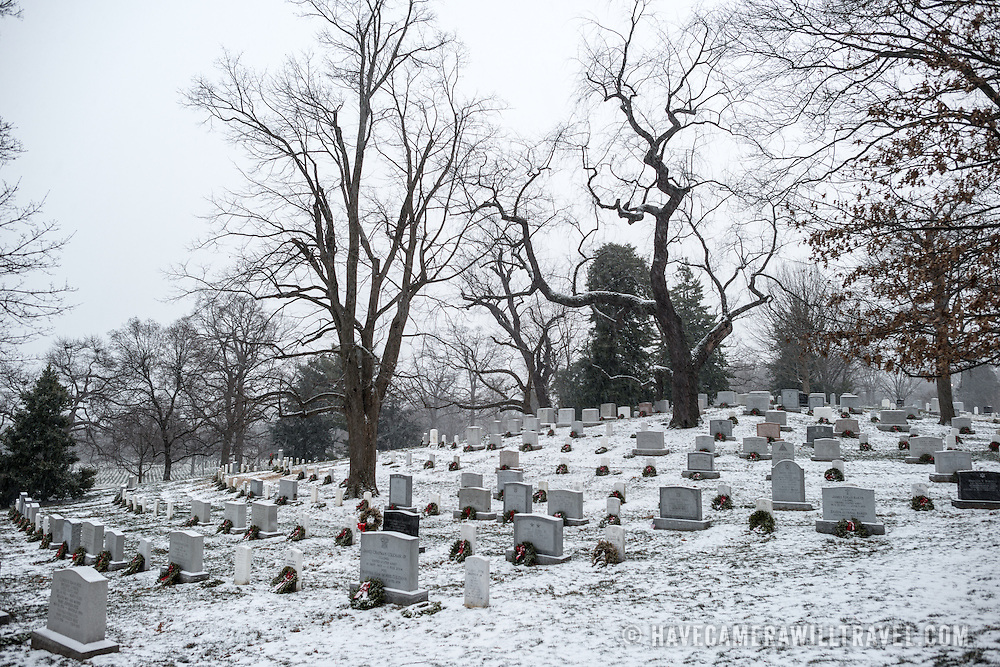 The ground of Arlington National Cemetery is covered in a light blanket of winter snow after recent snowfall.