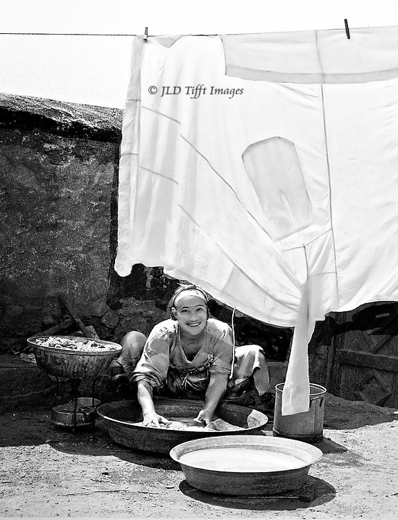 Cairene laundress outside her home; immaculate white galabeyya hanging to dry above her smiling face.