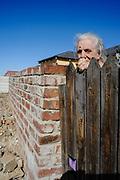 Een buurtbewoonster kijkt toe op de constructiewerken bij haar huis in Port Elizabeth.