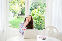 Exhaust young woman sitting in front of laptop