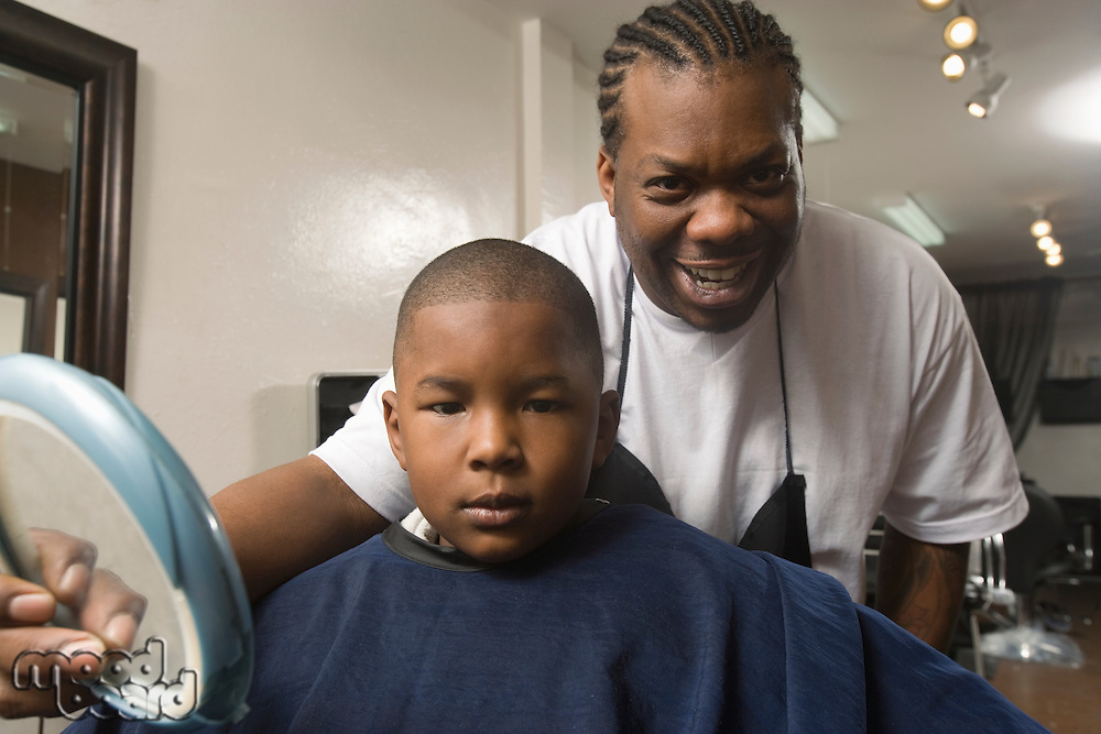 Young boy being shown his shaven head in the barbers