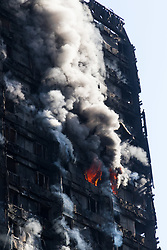 London, June 14th 2017. A fire rages through a residential tower block, Grenfell Tower, in Kensington, West London, with the entire building engulfed in flames. More than 200 firefighters are attending the incident and there are reports of people trapped inside. No figures are available as to casualties. PICTURED: Flames explode from one of the flats on the upper floors of the 27 storey building.