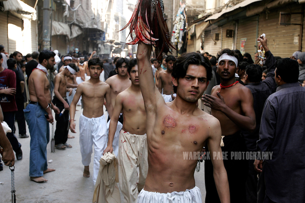 LAHORE, PAKISTAN - FEBRUARY 9: Shia Muslim walk proudly through a crowd after whipping themselves with chains and blades and offering the tools to anyone else who wishes to participate during the Shia Muslim observance of Ashura, February 9, 2006, Lahore, Pakistan. Millions of Muslims worldwide observe Ashura during the month of Muharram to mourn the death of the Prophet Mohammed's grandson Immam Hussain. Some Shia participate in self-flagellation to punish themselves for failing to protect the prophet's  grandson. Many Shia, however, see this act as unnecessary. During the month of Muharram, many Shia's give generously to the poor and spend time in prayer. (Photo by Warrick Page)