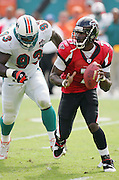 MIAMI - NOVEMBER 6:  Quarterback Michael Vick #7 of the Atlanta Falcons looks for a receiver as he avoids a tackle by defensive end Kevin Carter #93 of the Miami Dolphins on November 6, 2005 at Dolphins Stadium in Miami, Florida. The Falcons defeated the Dolphins 17-10. ©Paul Anthony Spinelli *** Local Caption *** Michael Vick;Kevin Carter