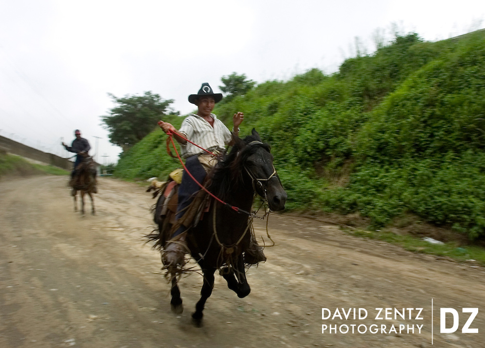 Young men on horseback barrel down a dirt road on the fringe of the small town of Jinotepe, Nicaragua on October 3, 2004.