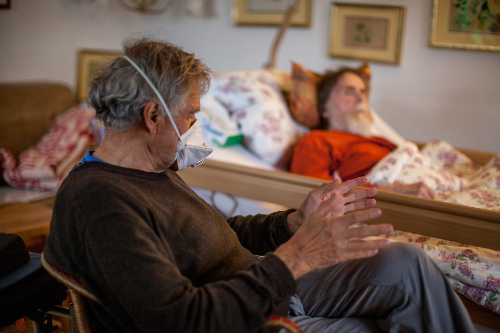 A sick pensioner in home care is getting visited by a friend who is wearing a face mask because of the corona virus danger.