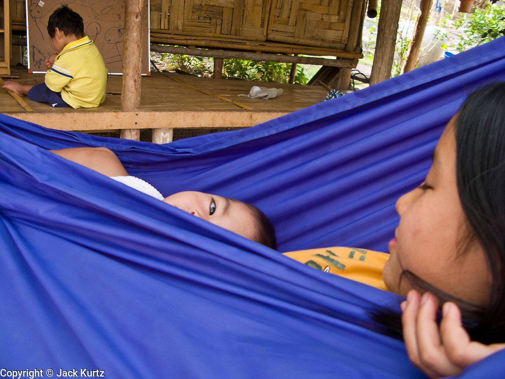 18 FEBRUARY 2008 -- BONG TI, KANCHANABURI, THAILAND: A Burmese child and his sister in a hammock at the Bamboo School in Bong Ti, Thailand, about 40 miles from the provincial capital of Kanchanaburi. Sixty three children, most members of the Karen hilltribe, a persecuted ethnic minority in Burma, live at the school under the care of Catherine Riley-Bryan, whom the locals call MomoCat (Momo is the Karen hilltribe word for mother). She provides housing, food and medical care for the kids and helps them get enrolled in nearby Thai public schools. Her compound is about a half mile from the Thai-Burma border. She also helps nearby Karen refugee villages by digging water wells for them and providing medical care.  Photo by Jack Kurtz