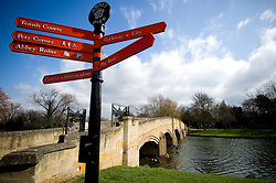 Signpost at the stone footbridge spanning the River Soar, Abbey Park, Leicester, England, UK.