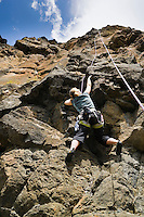 A female rock climber making her way up a steep rock wall.  Lava Point, Tieton River Climbing, Cascade Mountain, Washington, USA.