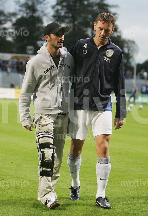 Jena , 271006 , Saison 2006/2007 ; Fussball 2.Bundesliga FC Carl Zeiss Jena - TuS Koblenz  Der verletzte Sercan GUEVENISIK und Krzystof KOWALIK (r.) (beide Jena)